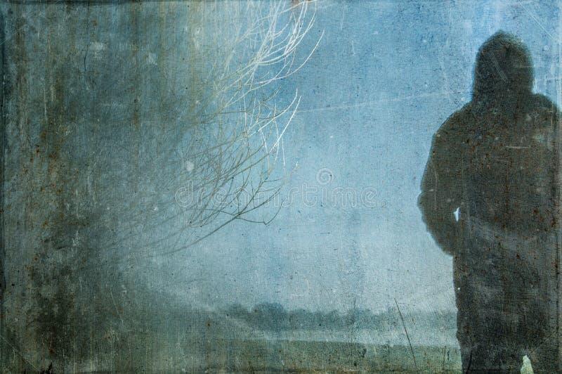 Una silueta misteriosa de una figura encapuchada solitaria en un campo con un extracto borroso oscuro, fantasmagórico, grunge, vi foto de archivo libre de regalías