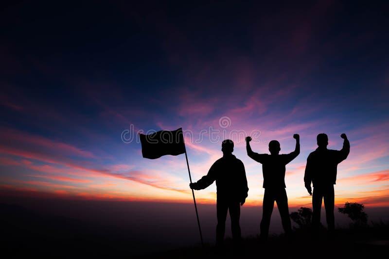 Una siluetta dei tre giovani che stanno sopra la montagna con i pugni si è alzata su e tenendo la bandiera sul fondo dell'alba fotografia stock libera da diritti