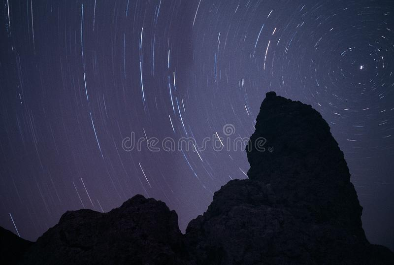 Una siluetta del tufo alla notte, retroilluminata dalle tracce della stella che circondano la stella polare fotografia stock libera da diritti