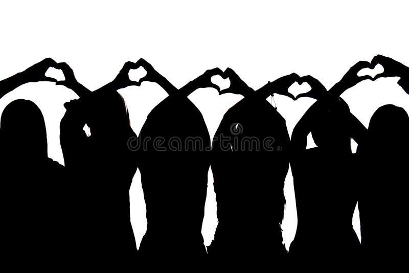 Una siluetta di cinque amici che mostrano i cuori con le loro mani fotografia stock libera da diritti