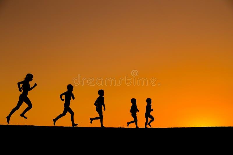 Una siluetta di cinque bambini correnti contro il tramonto immagini stock libere da diritti