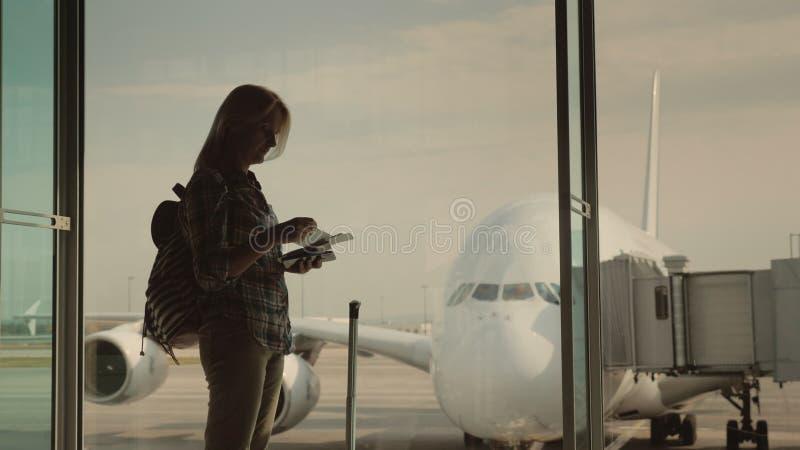 Una siluetta di una donna con i documenti di imbarco a disposizione, in attesa atterraggio sul suo volo Supporti alla finestra in fotografia stock libera da diritti