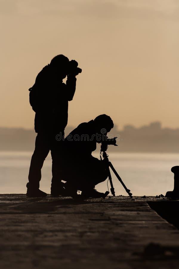 Una siluetta di due fotografi fotografia stock
