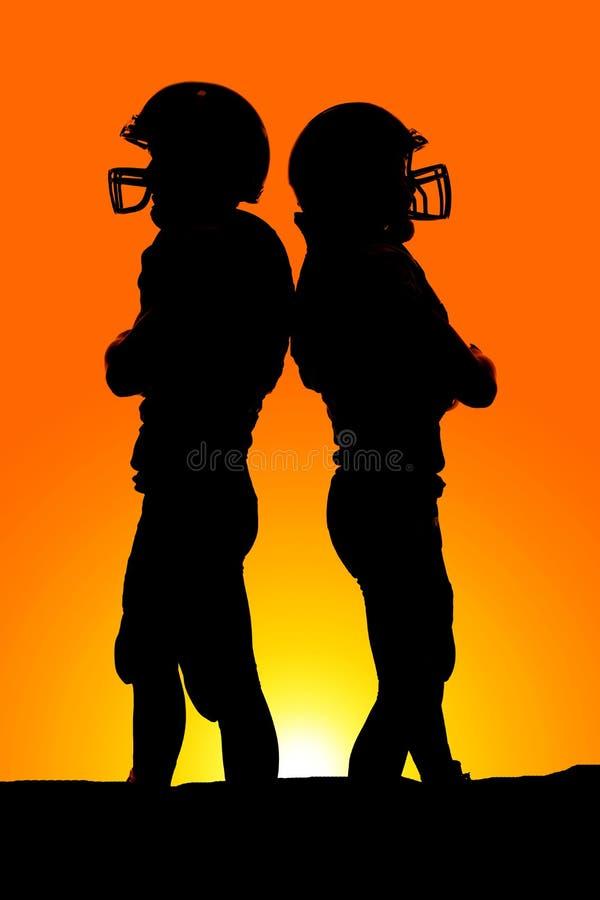 Una siluetta di due giocatori di football americano di nuovo alla parte posteriore fotografia stock libera da diritti