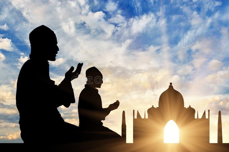 Una siluetta di due uomini che pregano al tramonto fotografia stock