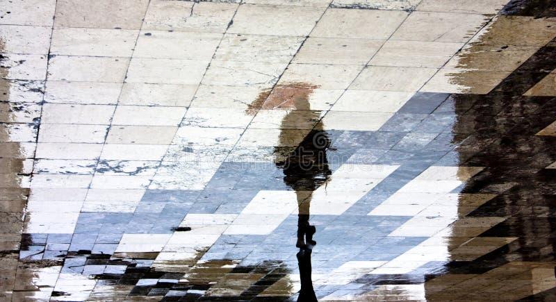 Una siluetta di riflessione di una donna con l'ombrello fotografie stock libere da diritti