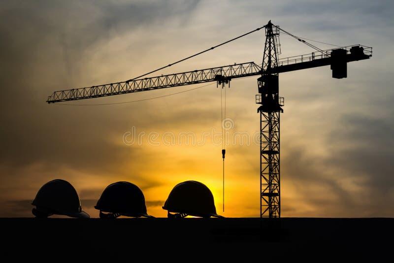 Una siluetta di tre caschi al cantiere con il fondo ed il tramonto della gru immagini stock libere da diritti