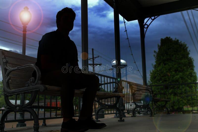 Una siluetta di un uomo che si siede su un banco fotografia stock libera da diritti