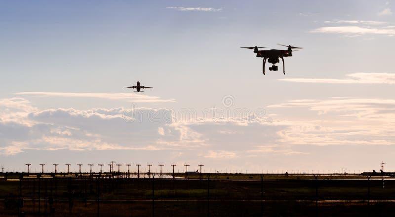 Una siluetta di un volo del fuco vicino ad un aeroporto con un aereo che parte nei precedenti immagini stock libere da diritti