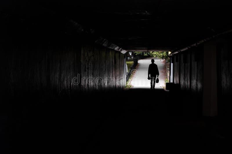 In una siluetta scura del tunnel di un uomo di camminata, nei precedenti degli alberi ed in un sentiero per pedoni fotografie stock libere da diritti