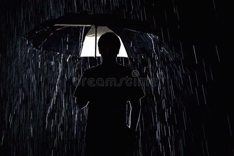 Una siluetta scura e piovosa fotografia stock