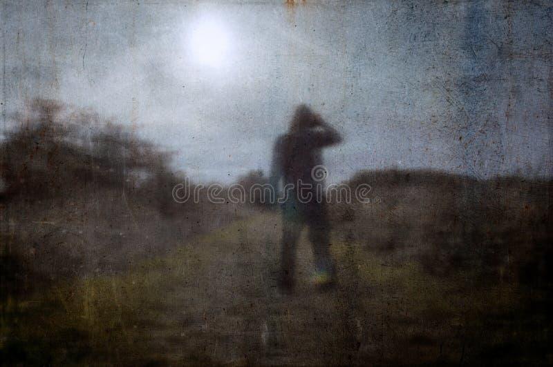 Una siluetta sinistra di una figura incappucciata sola in un campo su un percorso del paese Esaminando il sole Con un estratto va immagine stock