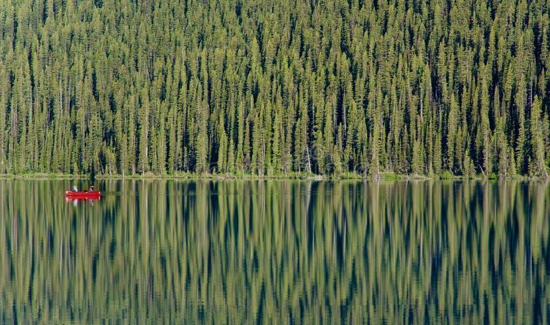 Una singola canoa rossa galleggia su un Lake Louise vetroso immagini stock