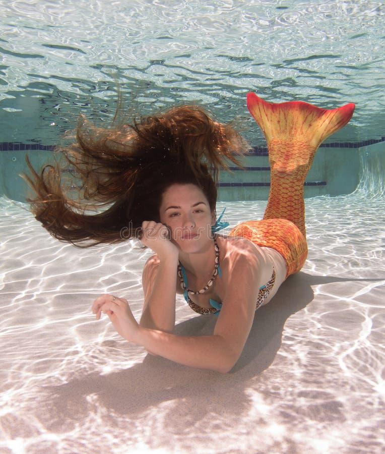 Una sirena con e una coda arancio subacquea fotografia stock