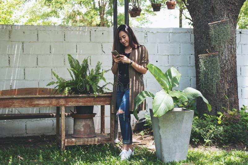 Una situación asiática hermosa de la mujer y usar el teléfono elegante con la naturaleza verde y el fondo blanco de pared de ladr foto de archivo