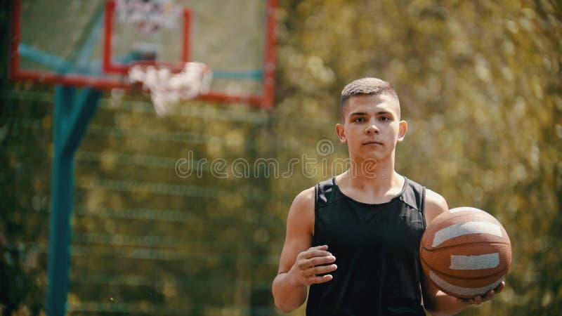 Una situación atlética joven del hombre en una tierra de deportes y sostener una bola del baloncesto imagen de archivo libre de regalías