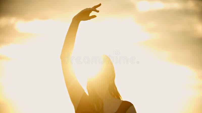 Una situación de la mujer joven en el tejado y aumenta su mano encima - de la puesta del sol brillante fotografía de archivo