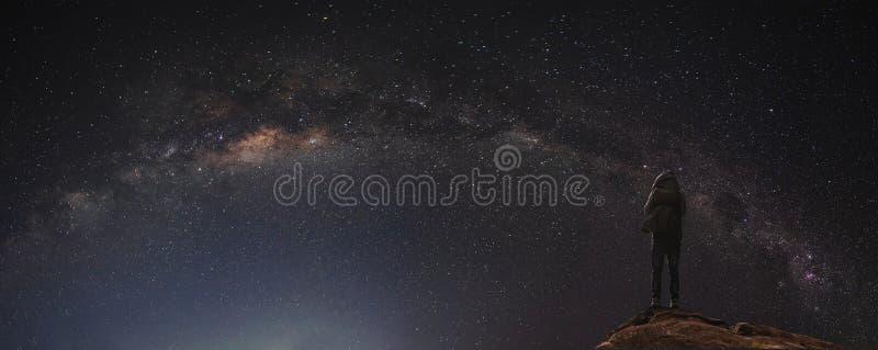 Una situación del hombre en la roca que disfruta del cielo y de la vía láctea estrellados en la noche imagenes de archivo