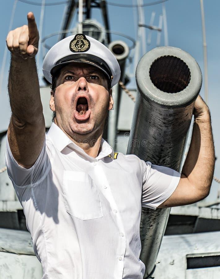 Una situación del oficial de la marina de guerra al lado del arma foto de archivo libre de regalías