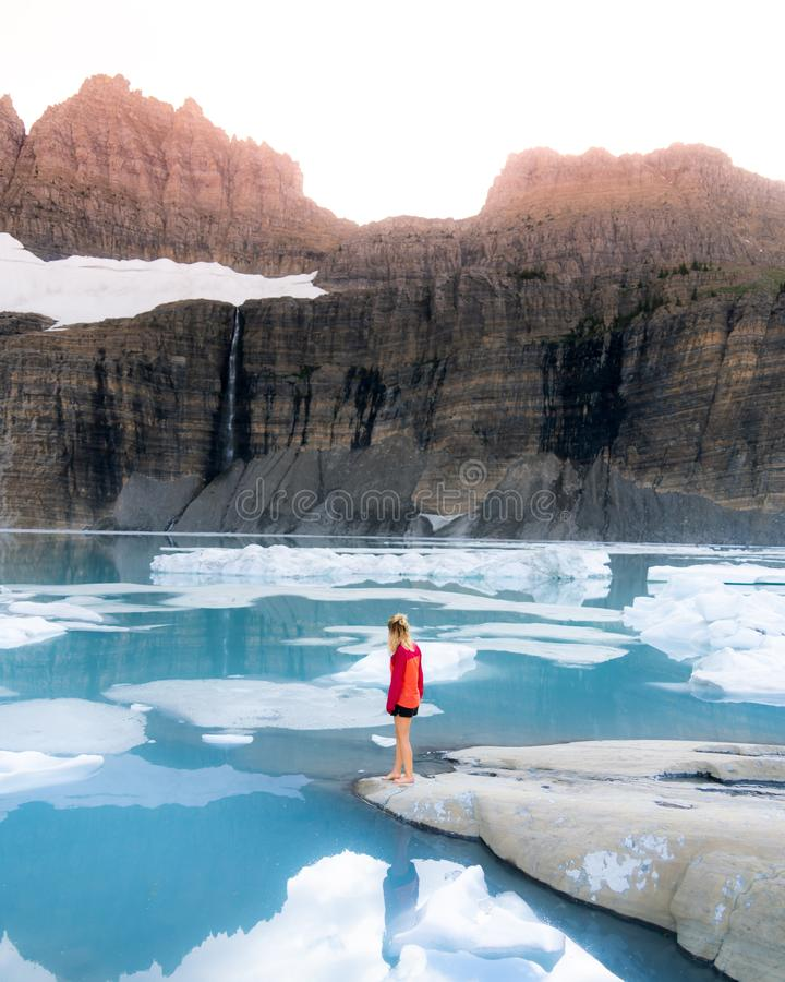 Una situaci?n femenina en rocas cerca de un lago hermoso congelado con las altas monta?as rocosas y nevosas fotos de archivo libres de regalías