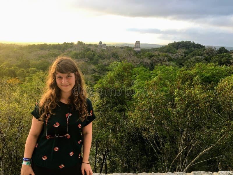 Una situación turística femenina joven delante de una opinión hermosa de la salida del sol de las ruinas y del templo IV de Tikal foto de archivo libre de regalías