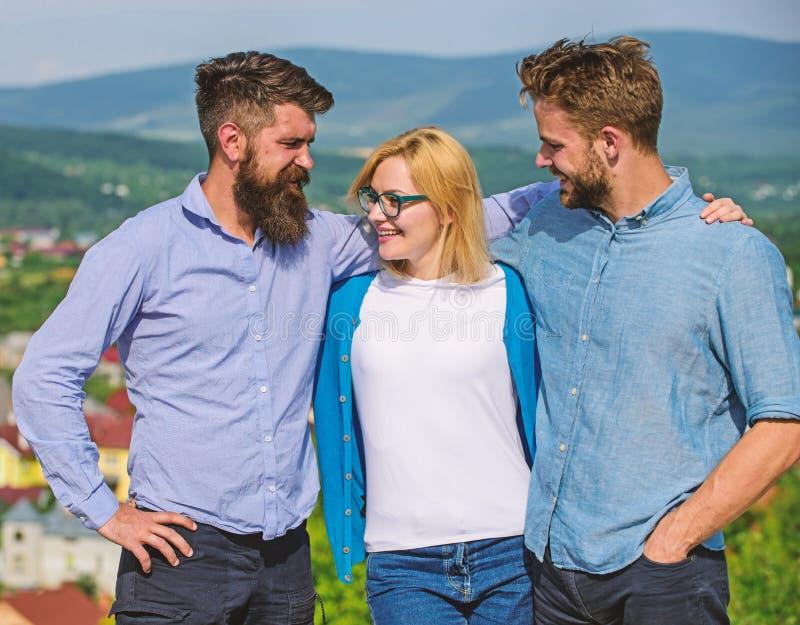 Una società di tre colleghi o partner felici abbraccia all'aperto, fondo della natura La società ha raggiunto la cima Squadra di  fotografia stock libera da diritti