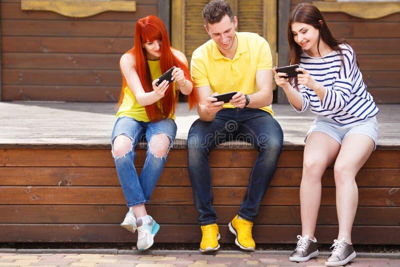 Una società di tre membri che giocano i giochi mobili immagine stock libera da diritti