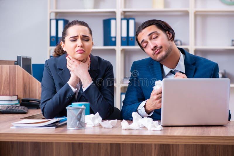 Una sofferenza dei due impiegati nel luogo di lavoro fotografia stock