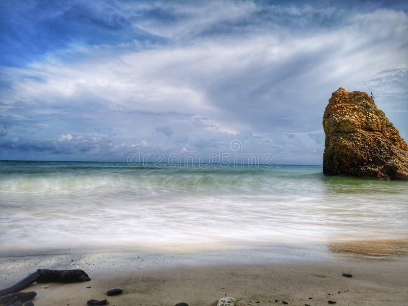 Una sola formación de roca hermosa y salpicar la reflexión lisa sedosa chapoteante del agua en la playa imagen de archivo libre de regalías