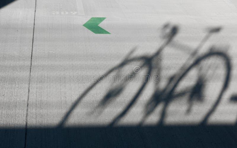 Una sombra de una bici del camino con una flecha verde fotos de archivo libres de regalías
