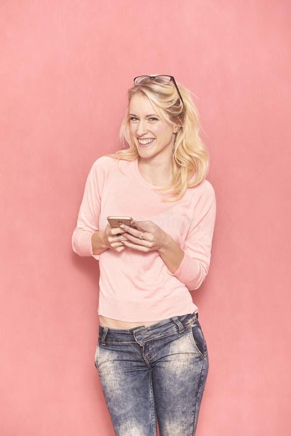 Una sonrisa de la mujer joven, mirando a la c?mara, mientras que manda un SMS o con a su smartphone, imagenes de archivo