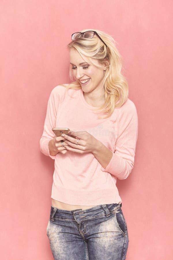 Una sonrisa de la mujer joven, mirando a la c?mara, mientras que manda un SMS o con a su smartphone fotografía de archivo libre de regalías