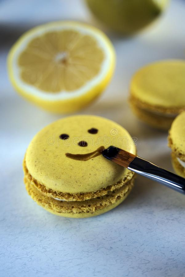 Una sonrisa hermosa en una galleta, pint? con una borla galletas amarillas de la Lim?n-almendra - un postre franc?s delicioso imagen de archivo