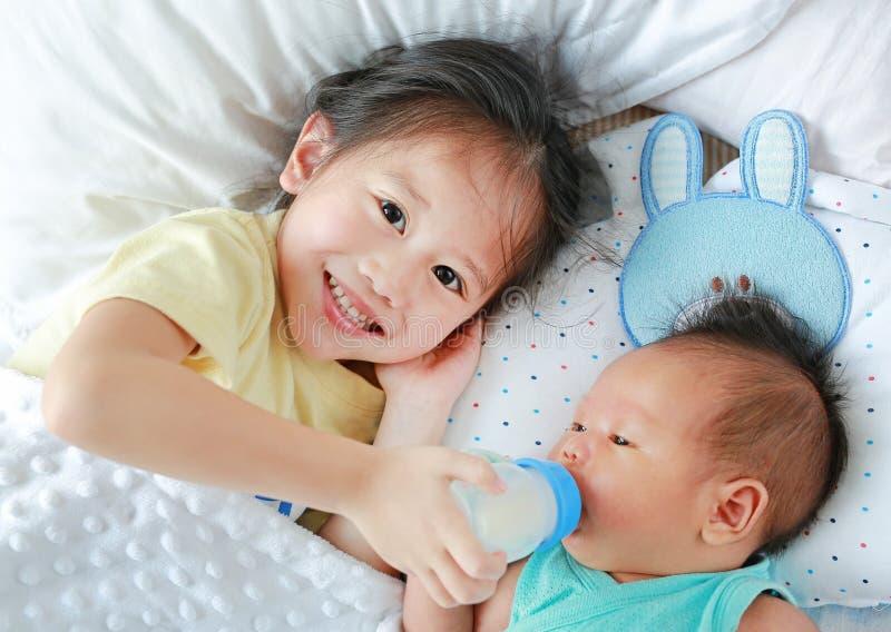 Una sorella felice che nutre del latte di bottiglia per il fratello e sta sdraiata sul letto immagini stock libere da diritti