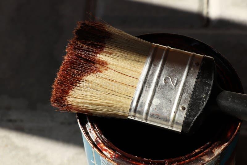 Una spazzola per legno di verniciatura ed alcuni bordi di legno con pittura fotografia stock