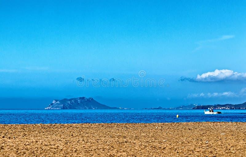 Una spiaggia pietrosa che guarda fuori ad un'isola fotografia stock libera da diritti