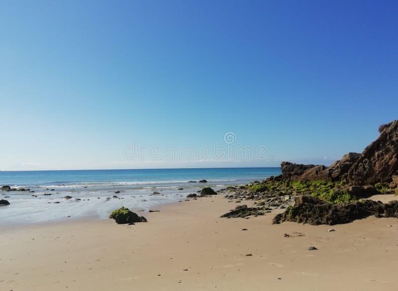 Una spiaggia sabbiosa vicino alle rocce fotografia stock