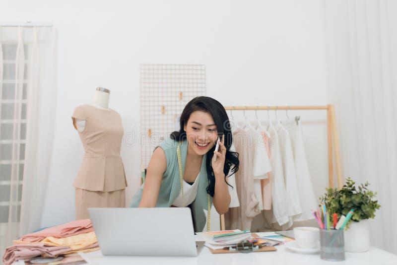 Una splendida sarta che usa il portatile e telefona mentre lavora al suo laboratorio Dressmaker con laptop immagini stock libere da diritti