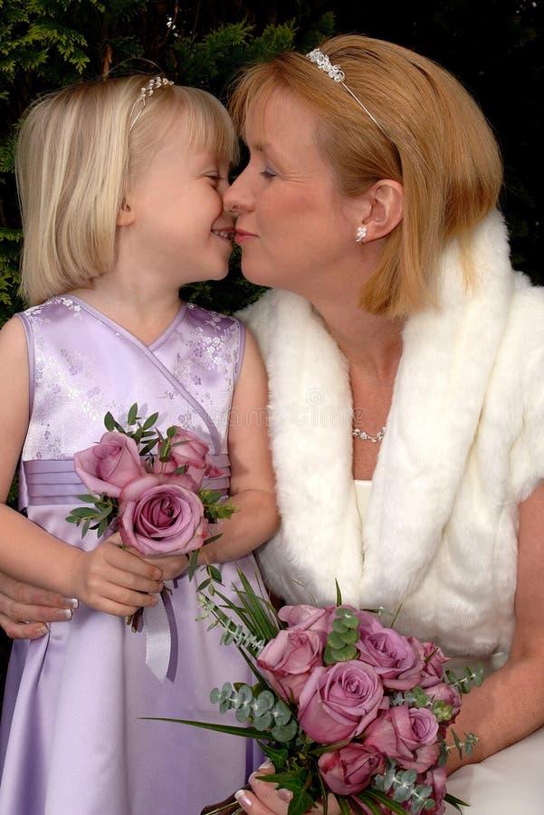 Una sposa e una damigella d'onore che ripartono un momento tenero su un giorno delle nozze fotografia stock