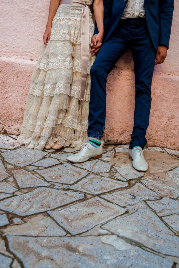 Una sposa e uno sposo delle coppie dei pantaloni a vita bassa con i calzini funky colorati e un vestito da sposa d'annata immagini stock