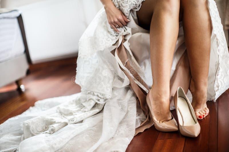 Una sposa mette sopra il suo primo piano dei tacchi alti Sta portando il suo vestito da sposa bianco fotografie stock libere da diritti