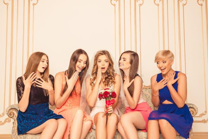 Una sposa piuttosto sorpresa con delle ragazze sedute sul divano fotografia stock