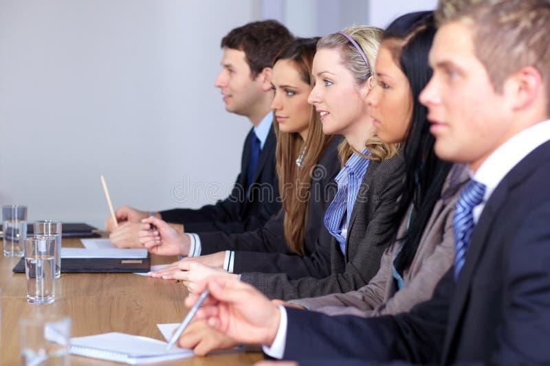 Una squadra di 5 genti che si siedono alla tabella di congresso immagine stock