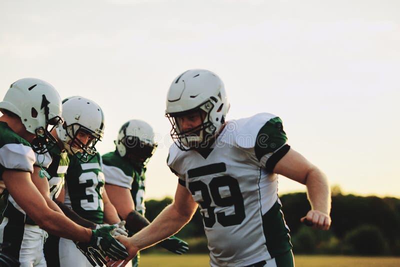Una squadra di football americano che festeggia con un cinque basso dopo una partita fotografie stock