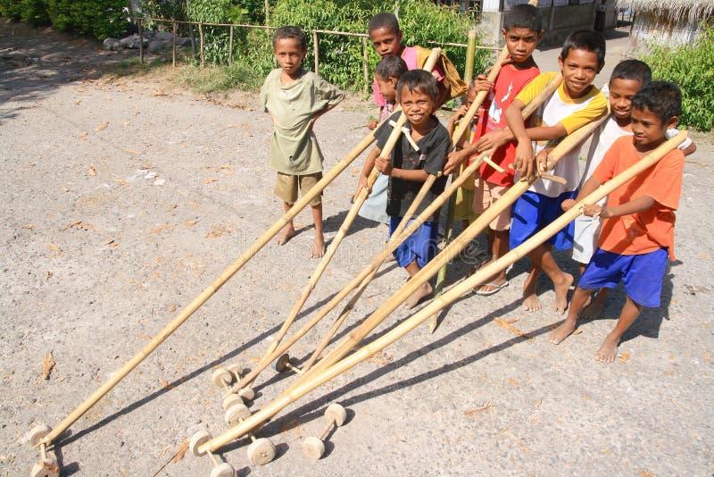Una squadra di ragazzi con i giocattoli di bambù in Indonesia fotografie stock libere da diritti