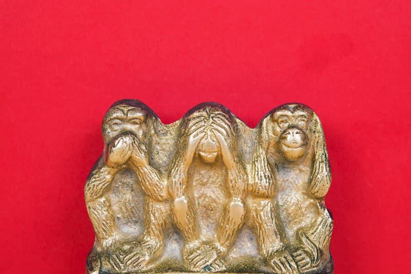 Una statua d'ottone di tre scimmie isolate su superficie di legno fotografie stock libere da diritti