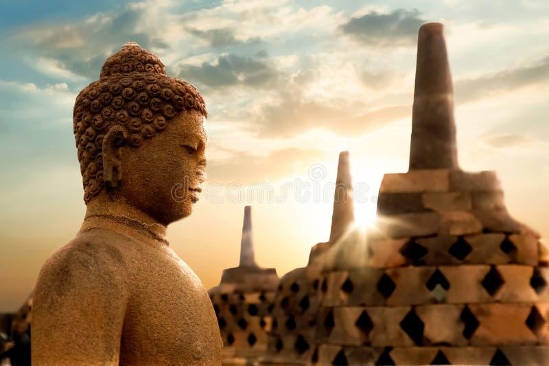 Una statua di Buddha contro lo sfondo dell'alba nel tempio di Borobudur Java Island l'indonesia immagini stock