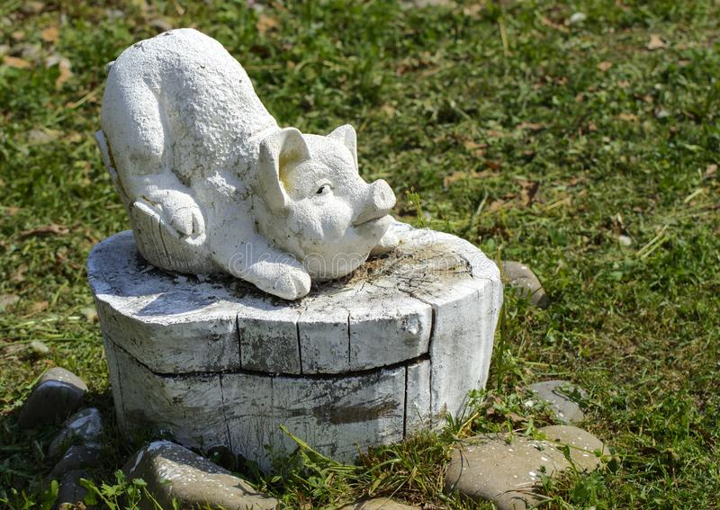 Una statua di un maiale fatto dei supporti di pietra su un ceppo di legno ha dipinto fotografia stock libera da diritti