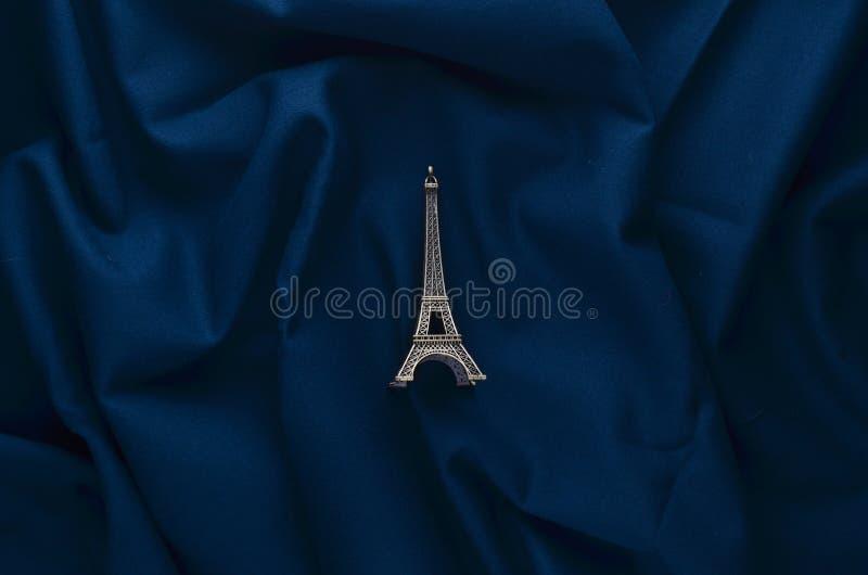 Una statuetta miniatura della torre Eiffel su un fondo blu scuro del panno Ricordo da Parigi Minimalismo di tendenza fotografia stock libera da diritti