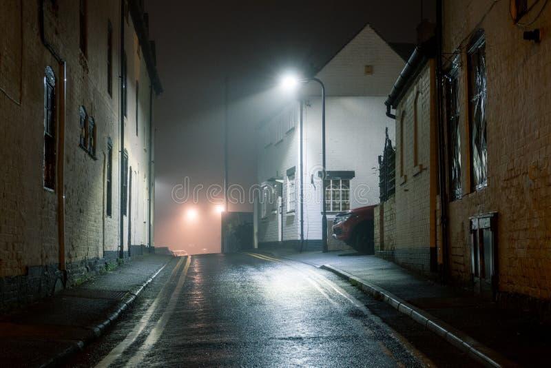 Una strada bagnata con edifici storici con luci di strada che brillano in una notte di inverni nebbiosi Upton upon Severn, Regno  immagini stock libere da diritti